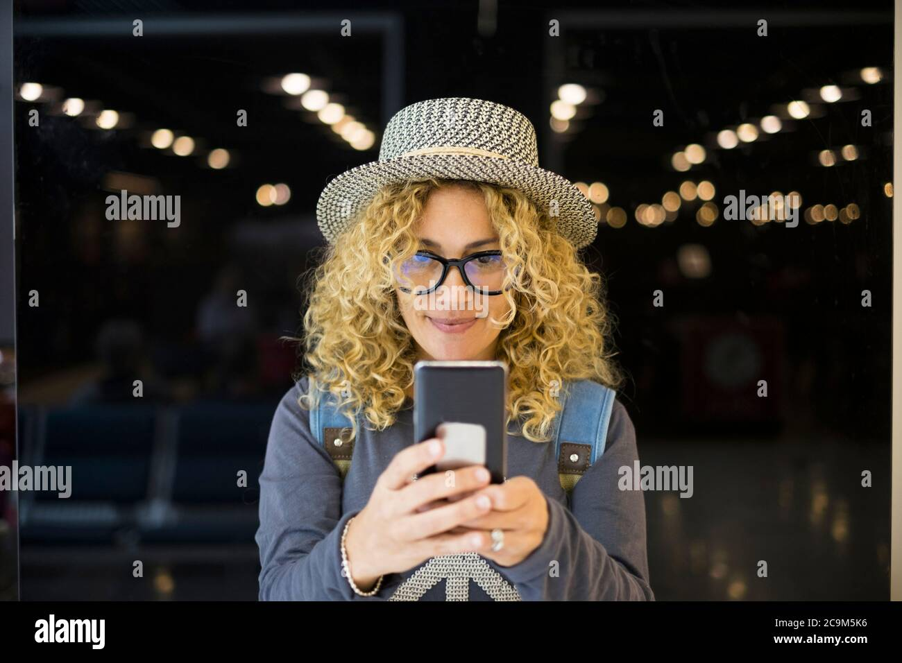 portrait and close up of beautiful curly and blonde woman looking at the camera smiling - happy people traveling at the airport - vacations outdoors Stock Photo