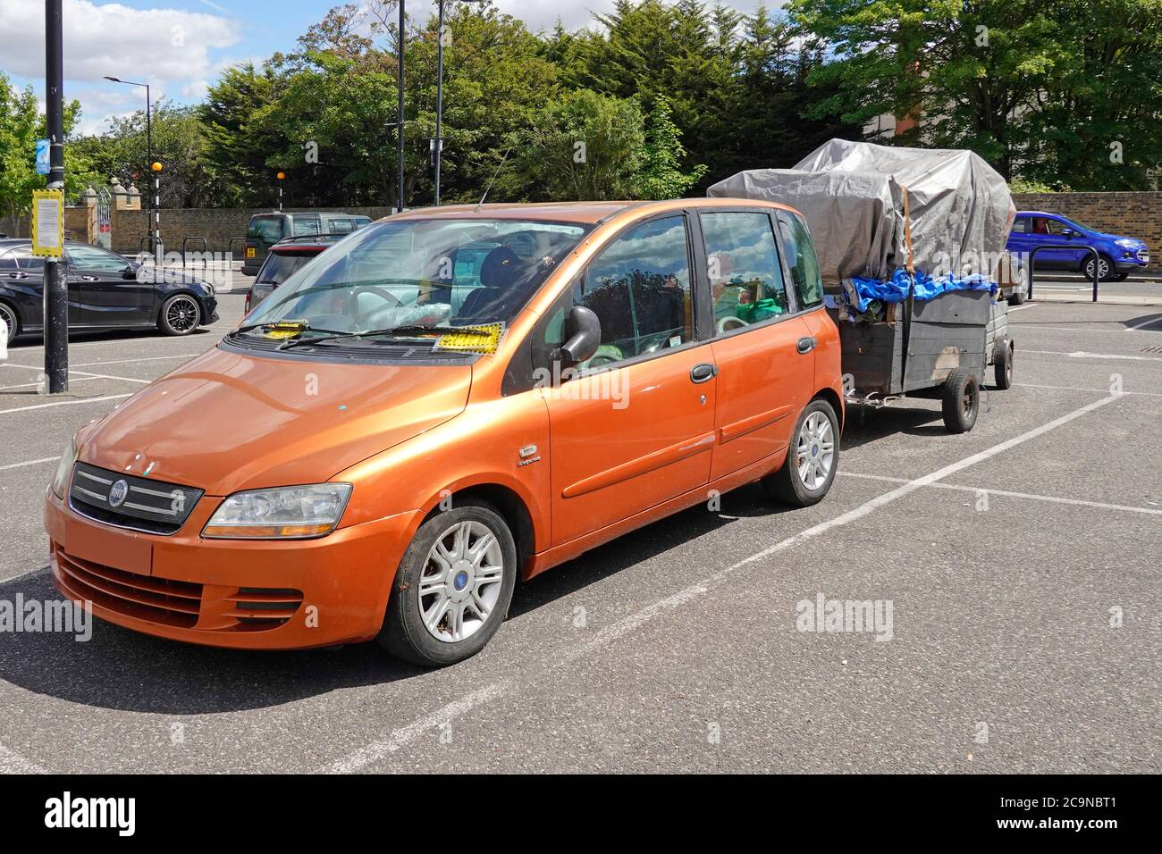 Misfortunes maybe or  expensive mistake parking chattels inside car & two loaded trailers in two bays of pay & display car park lot Essex England UK Stock Photo