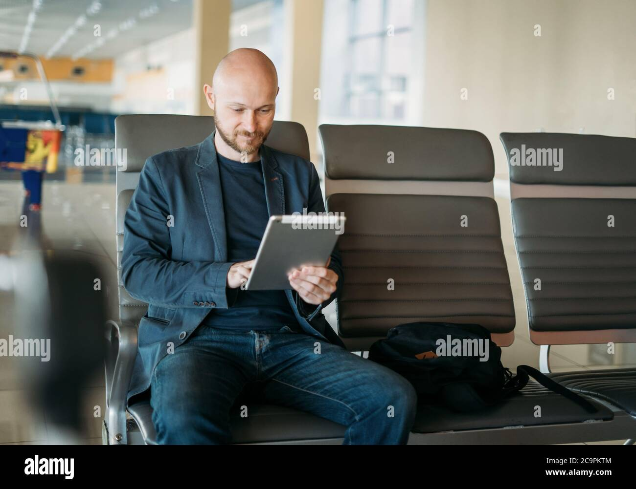 Handsome adult bald bearded man businessman in suit using tablet at airport lounge Stock Photo