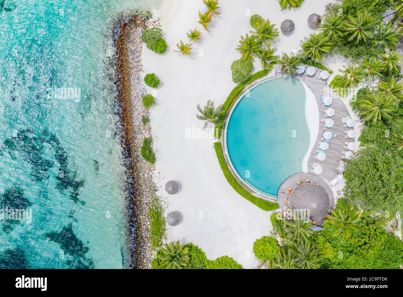 Top view from drone at beach, azure sea and poolside with palm tree in Maldives luxury resort. Tropical island, exotic aerial landscape Stock Photo