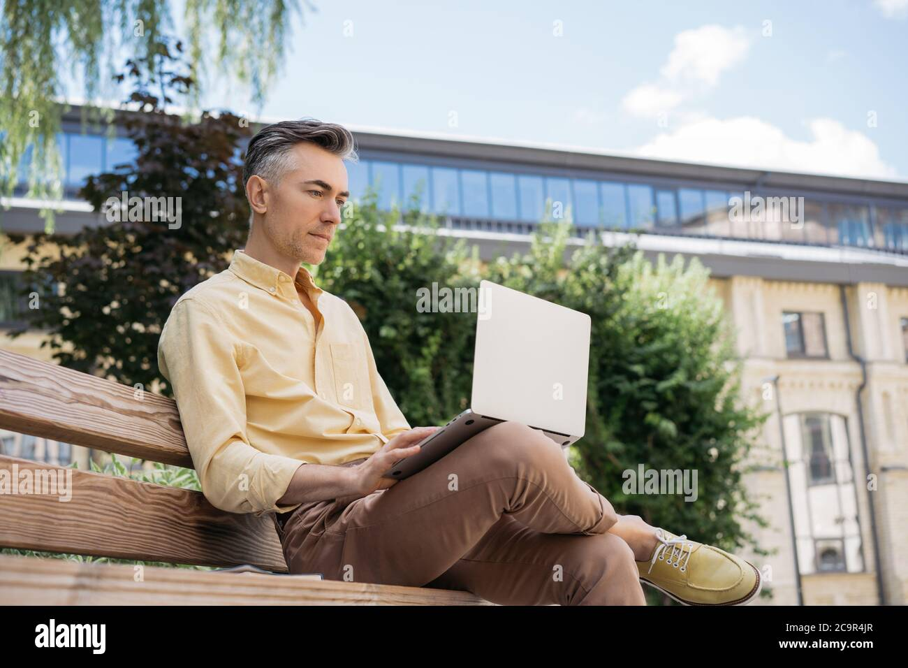 Serious mature businessman using laptop computer, planning start up, brainstorming, sitting outdoors. Busy freelancer working in park Stock Photo