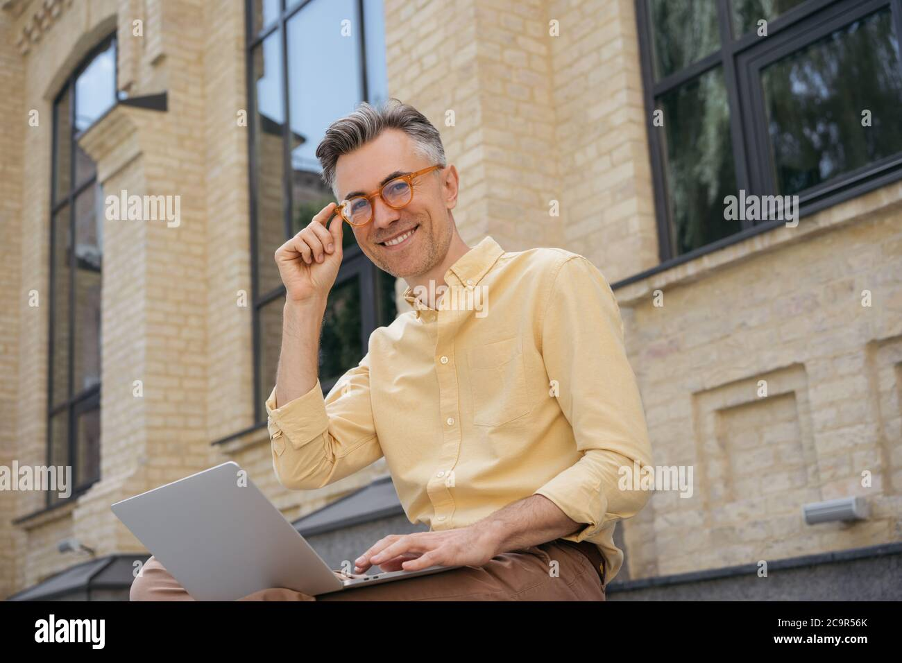 Portrait of handsome mature man working project, sitting outdoors. Confident freelancer copywriter using laptop computer, looking at camera Stock Photo