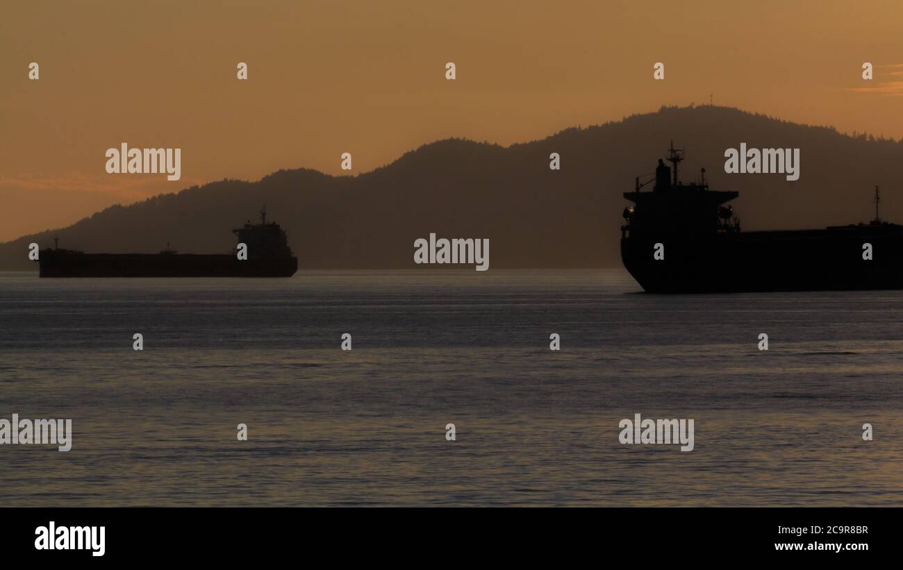 Cargo ferries during sunset by English Bay Vancouver, Canada Stock Photo