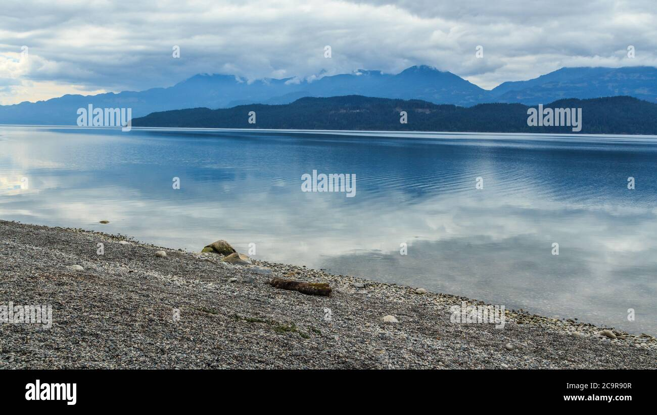Camping side lake in Vancouver surrounded by mountains during summer day as the clouds are reflecting in the water Stock Photo
