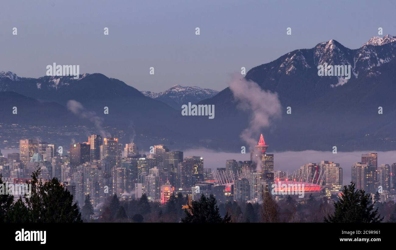Vancouver's skyline at night - Aerial view from the Queens Elizabeth park in winter with snowed mountains in the background Stock Photo