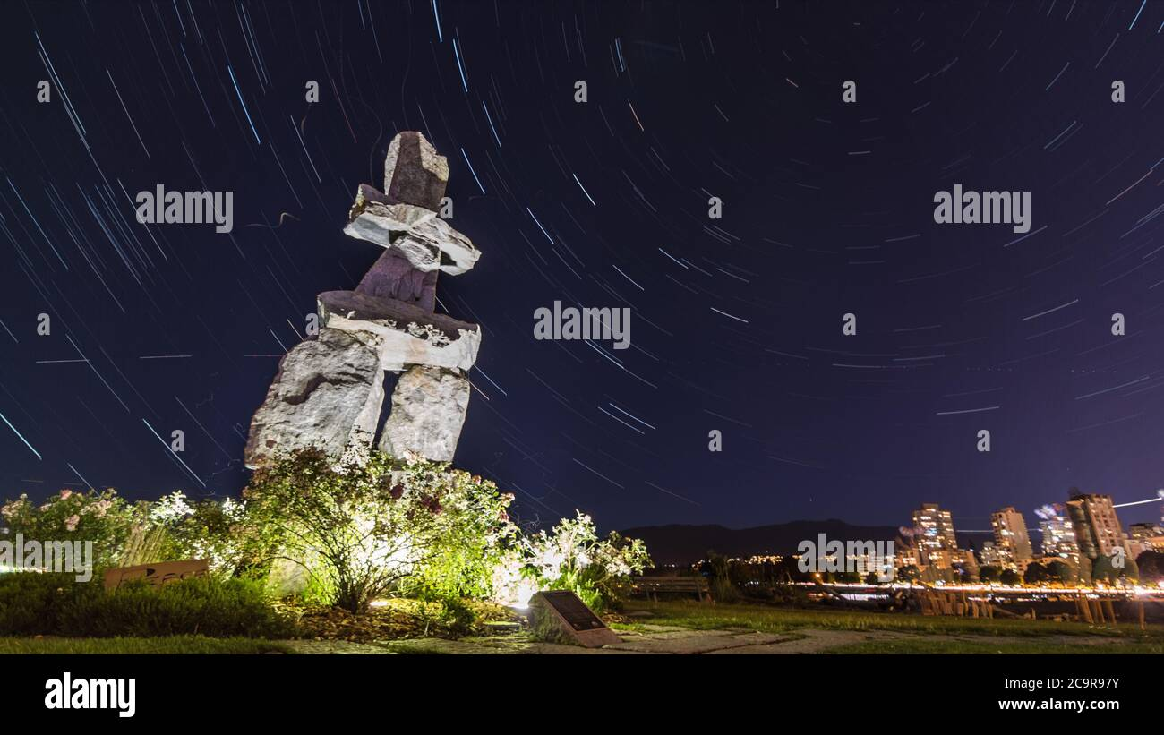 Inukshuk at Stanley Park, English Bay Beach, Vancouver, British Columbia, Canada, North America at night with star trails Stock Photo