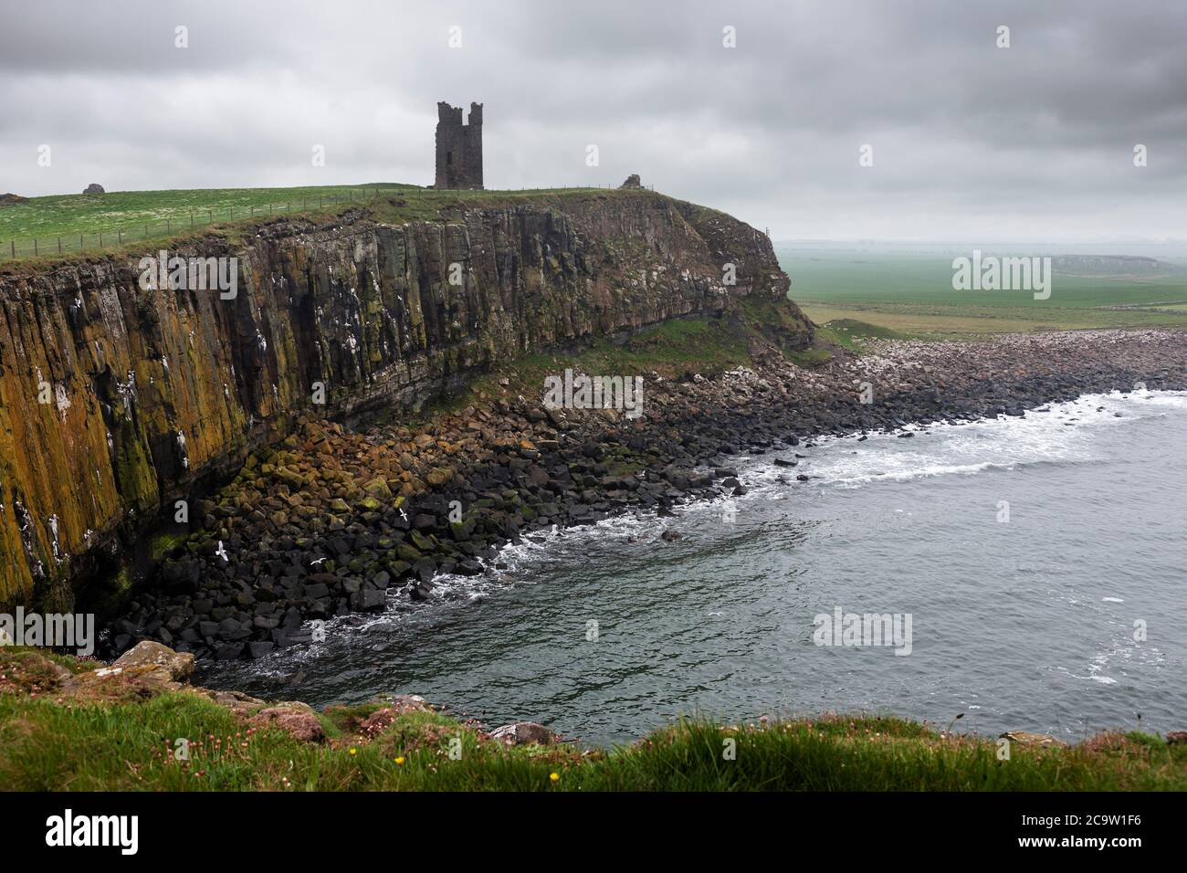The Gull Crag cliffs and the ruined Lilburn Tower, Dunstanburgh Castle, Northumberland, England, UK, from Castle Point on an overcast, gloomy day Stock Photo