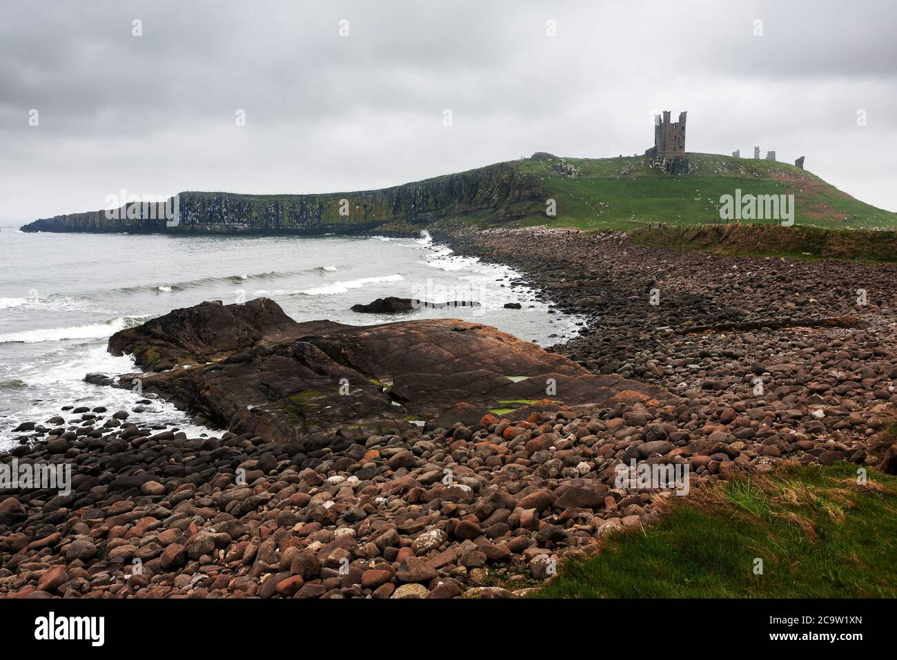 The ruins of Dunstanburgh Castle, Northumberland from Embleton Bay Stock Photo