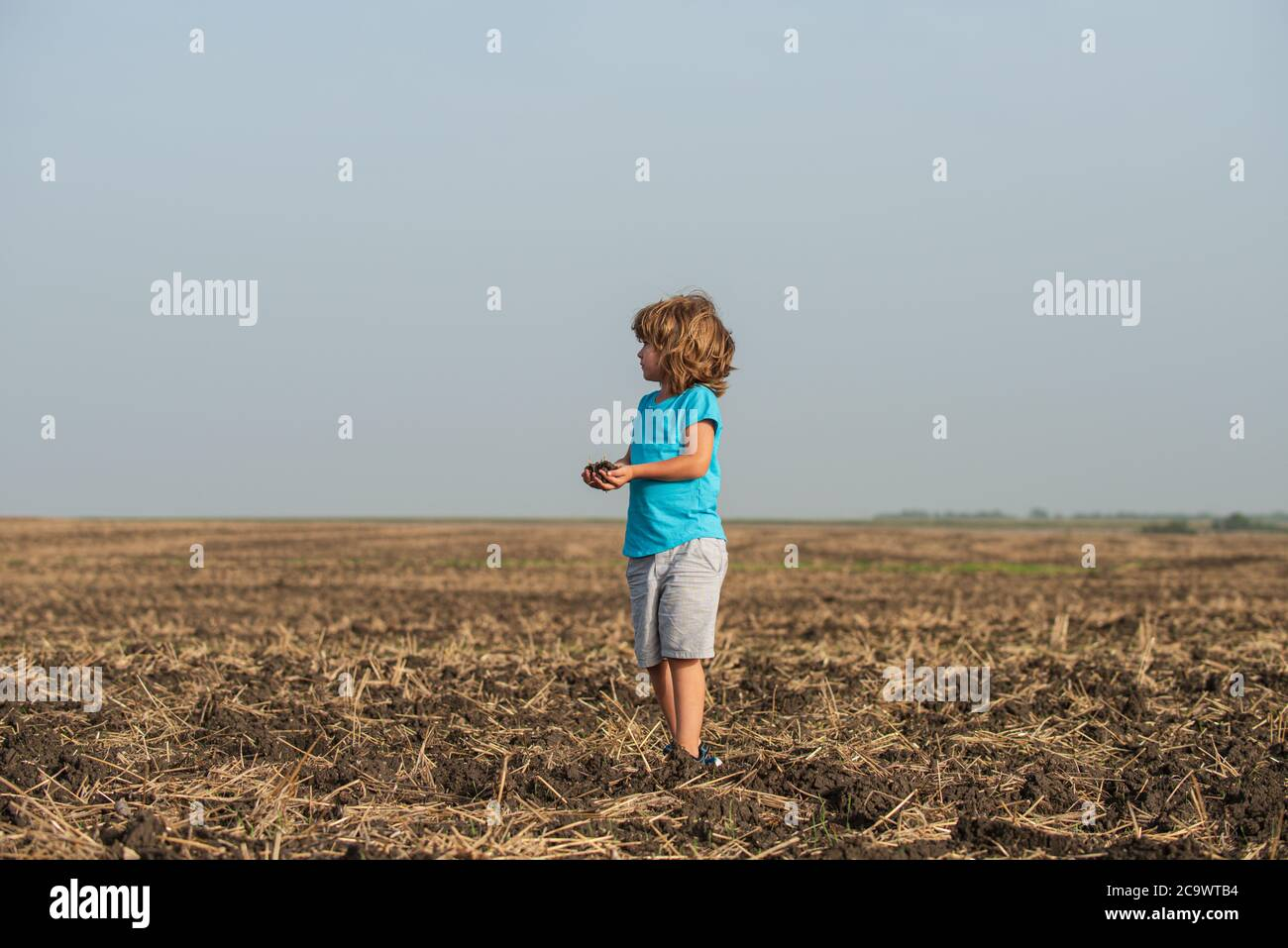 Cute little child farmer working on field. Ecology planting on land. Black soil on child hand. Earth day concept. Summer at countryside. Nature and Stock Photo