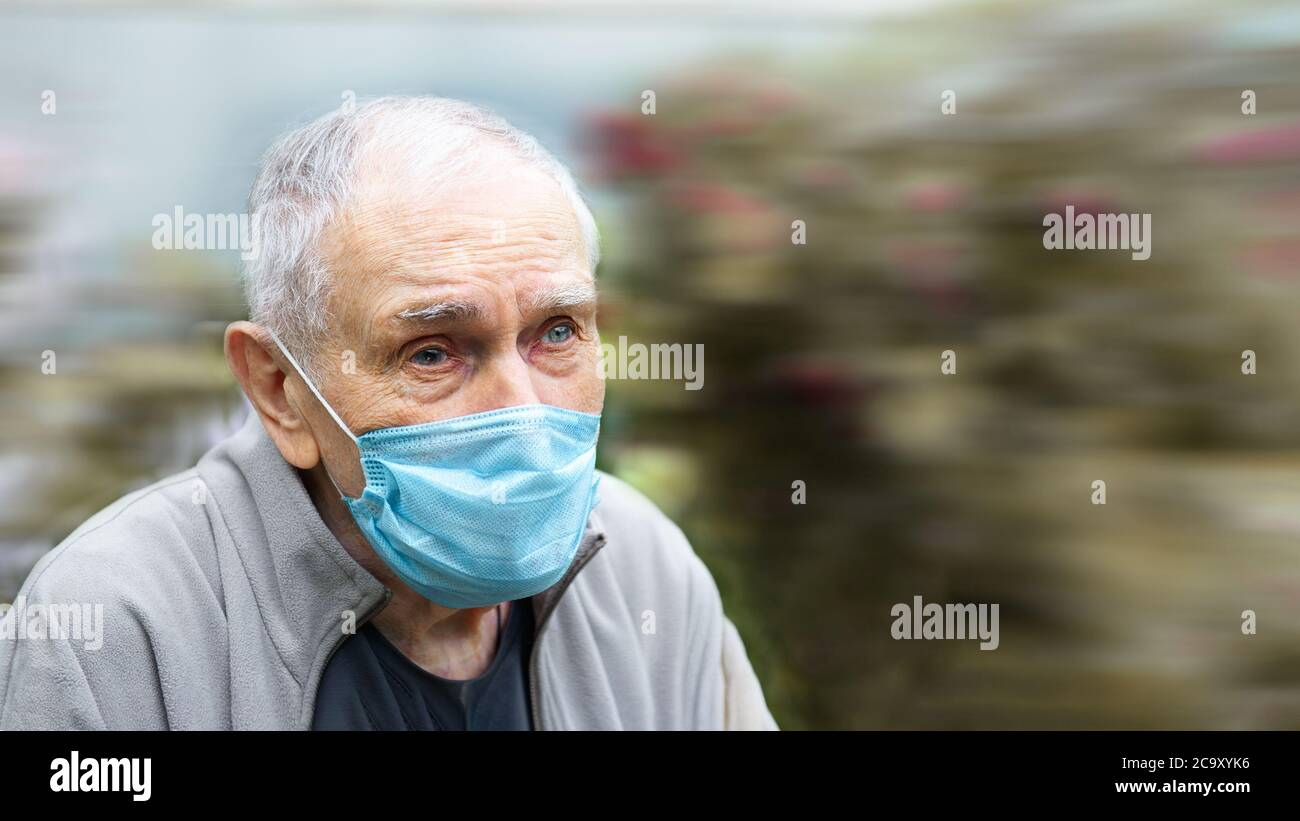 old man in a medical mask. old man wears a mask outdoors to avoid getting infected with the Corvette-19 virus. Prevention of viral diseases in the Stock Photo