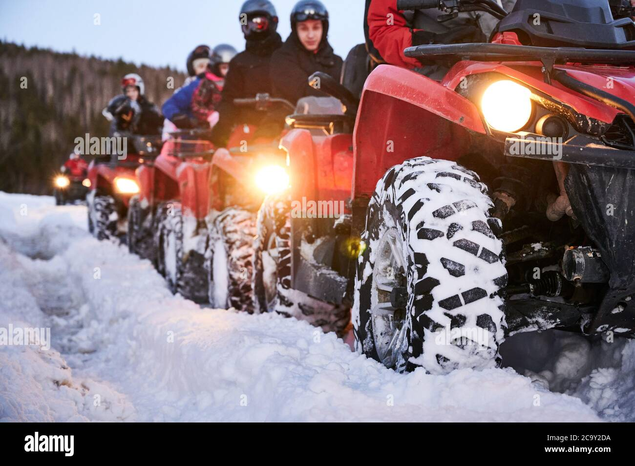 Focus on the wheel. People riding red all-terrain vehicles down snowy hill. Quad riders driving quad bikes with black snowy wheels on snow-covered trail. Concept of winter activities and quad biking. Stock Photo
