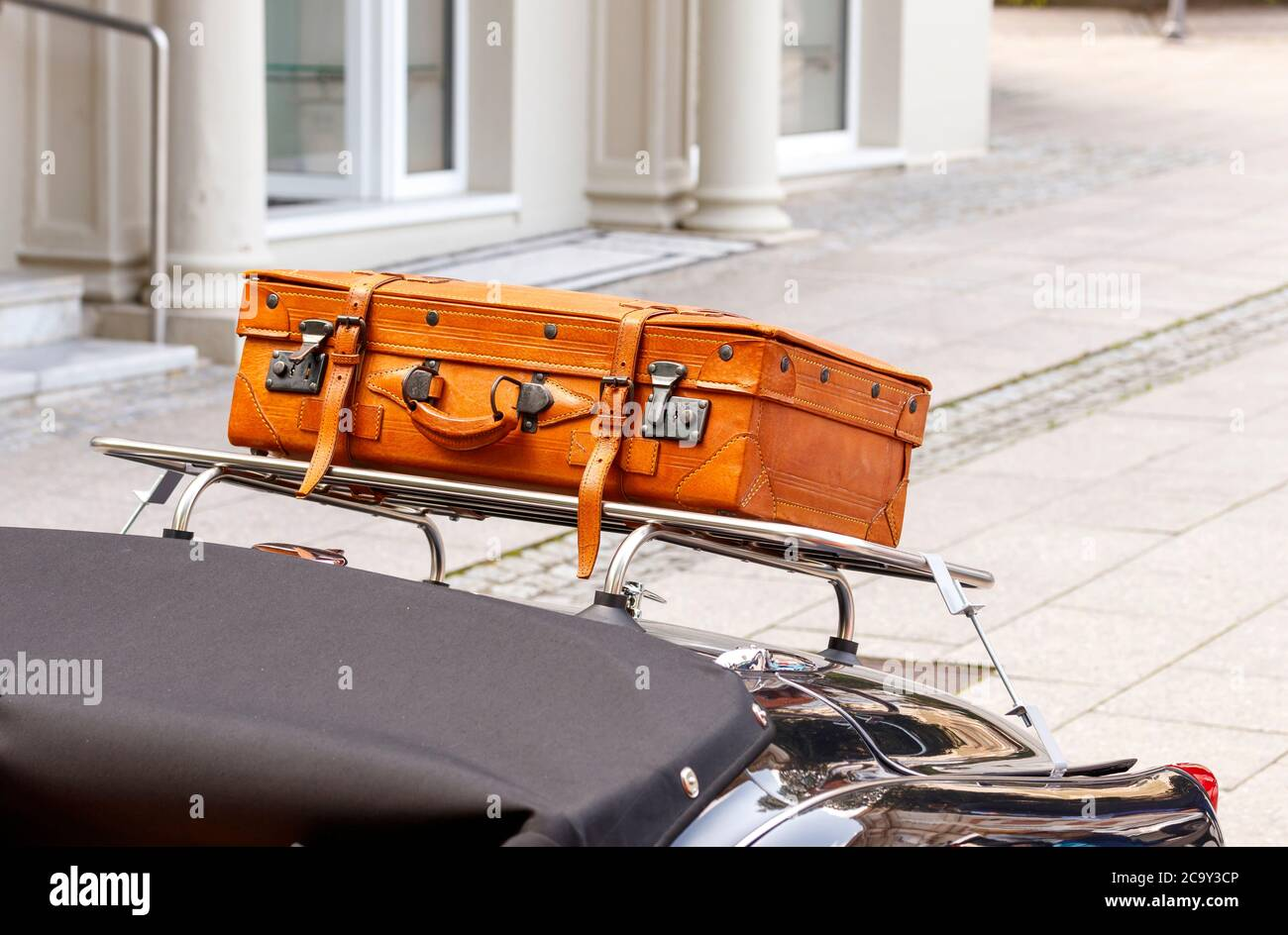 Leather suitcase on a luggage rack Stock Photo