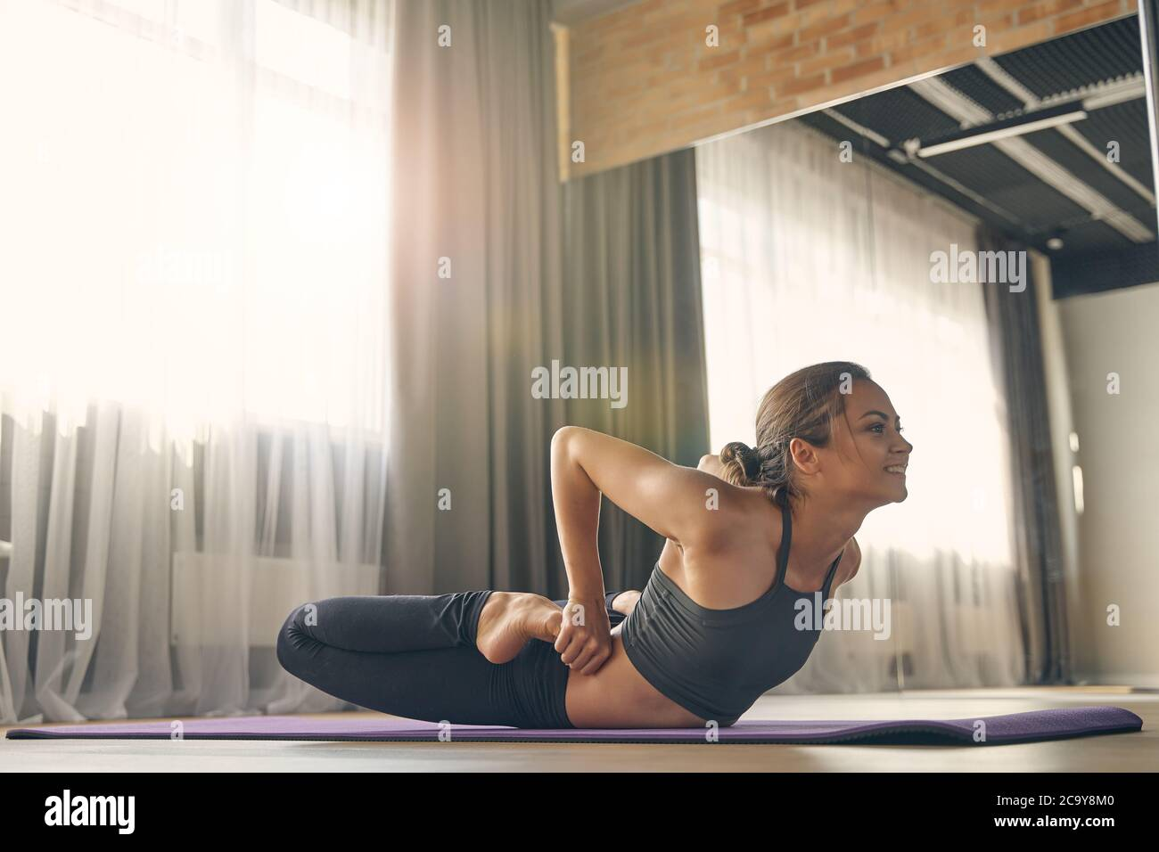 Smiling young woman practicing yoga in studio Stock Photo