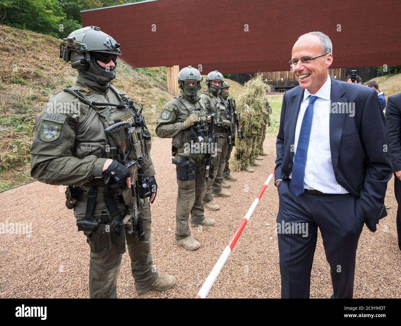 Lorch, Germany. 03rd Aug, 2020. Officials of the Special Operations Command (SEK) and Peter Beuth (CDU), Minister of the Interior of Hesse, stand side by side. The Hessian police are opening a modernized shooting range for training on police medium-range weapons. Credit: Andreas Arnold/dpa/Alamy Live News Stock Photo