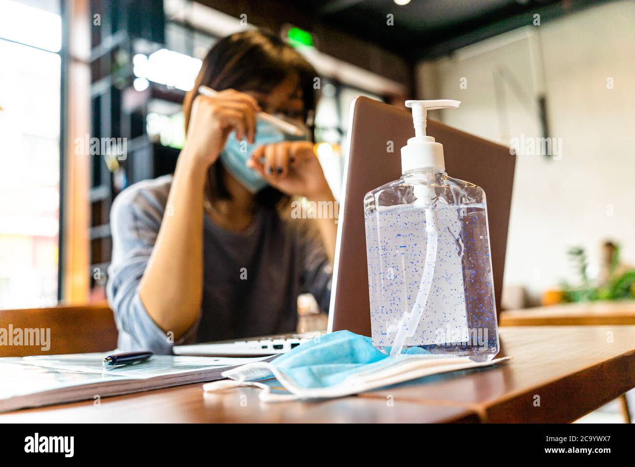 Young asian woman using laptop computer working at home with alcohol gel in quarantine for coronavirus wearing protective mask with social distancing Stock Photo