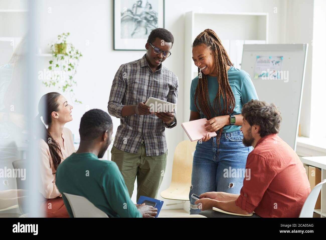 Multi-ethnic group of people sitting in circle while discussing business project in office, focus on smiling African-American woman talking to colleague standing up , copy space Stock Photo