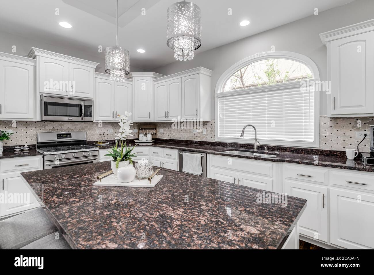 A Large Luxurious White Kitchen With A Brown And Black Granite Counter Top And Fancy Lights Hanging Over The Island Stock Photo Alamy