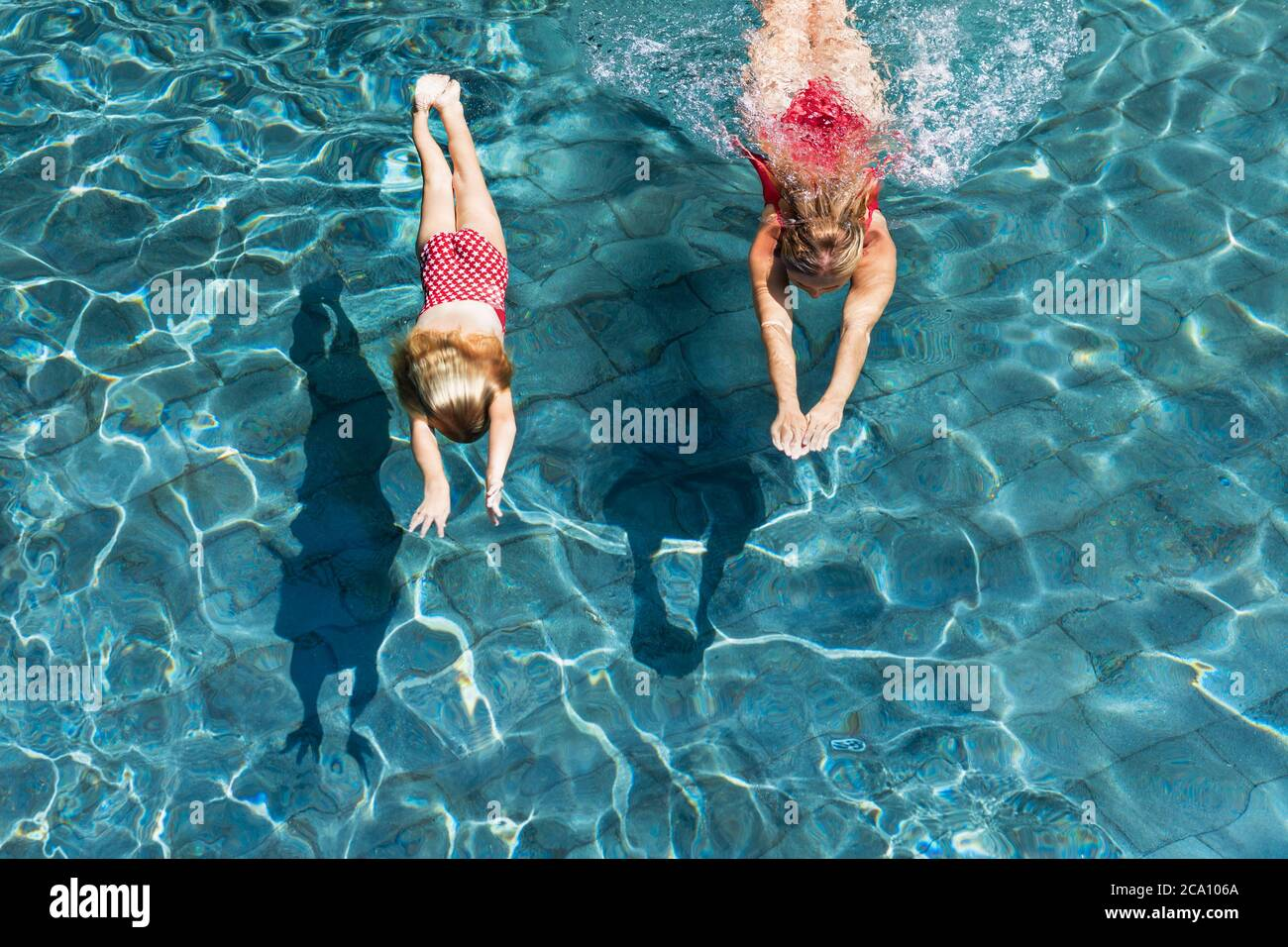 Happy family in swimming pool. Child with young woman swim, dive in pool with fun - jump deep down underwater. Healthy lifestyle, people water sport Stock Photo