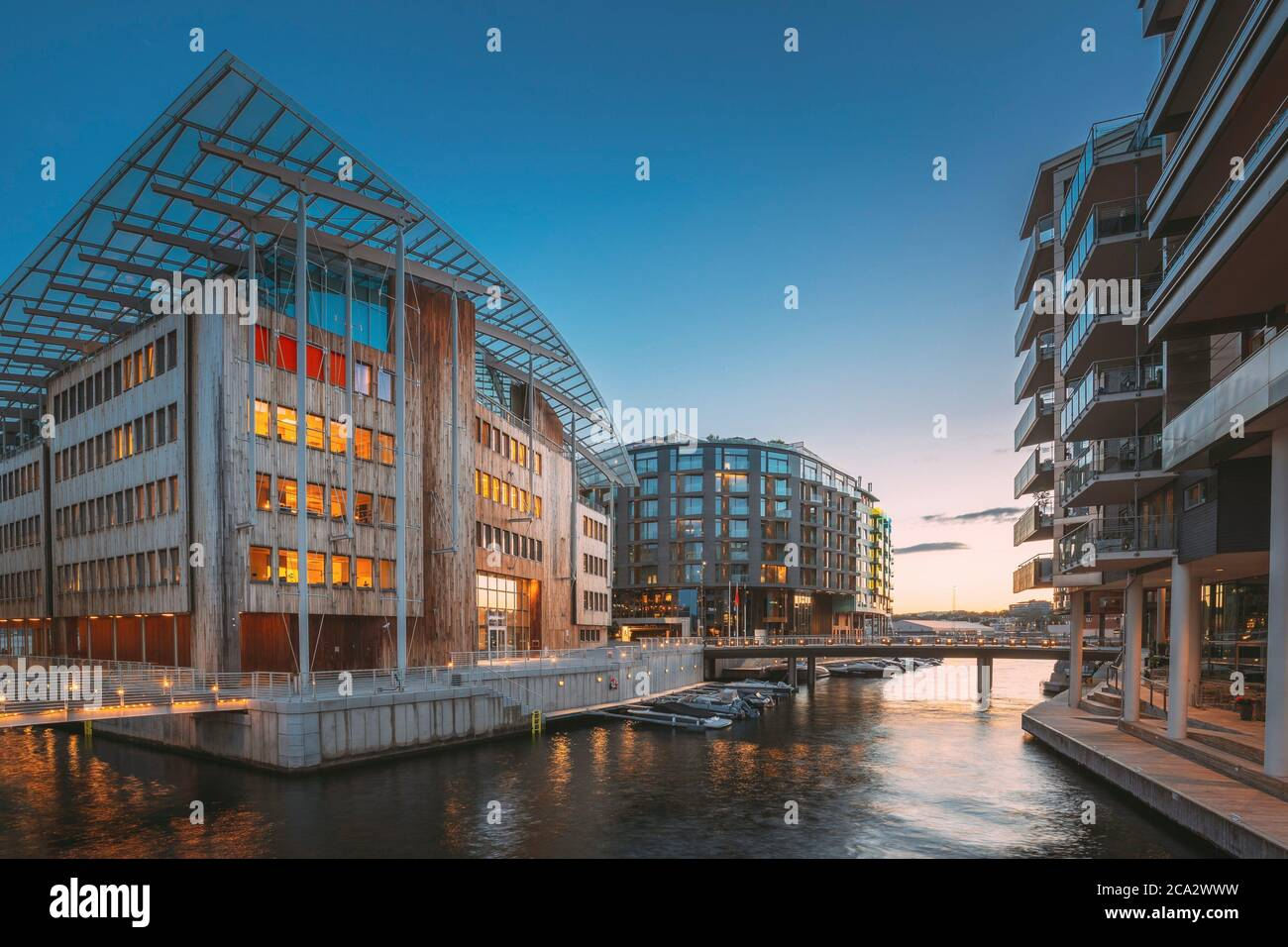 Oslo, Norway. Night View Embankment And Residential Multi-storey Houses In Aker Brygge District. Summer Evening. Residential Area Reflected In Sea Stock Photo