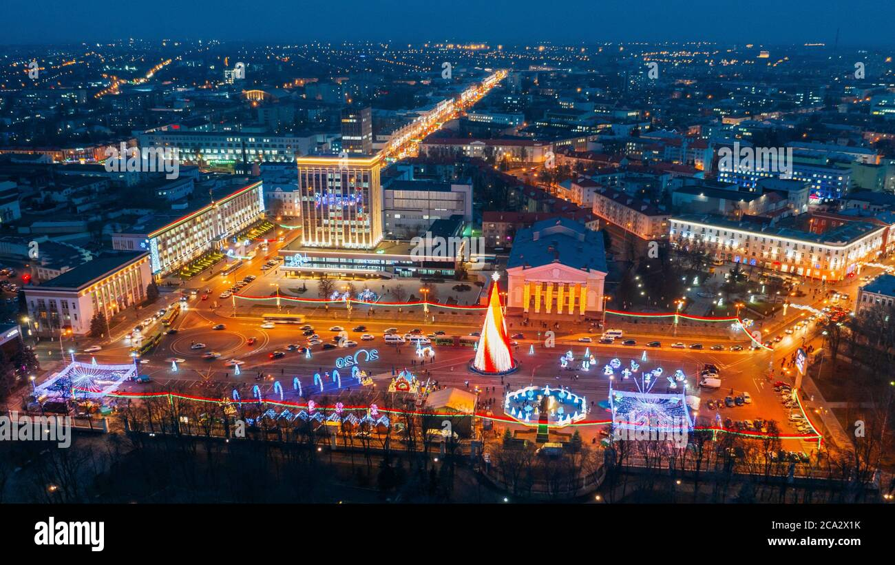 Gomel, Belarus. Main Christmas Tree And Festive Illumination On Lenin Square In Homel. New Year Celebration In Belarus. Aerial Night View. Stock Photo