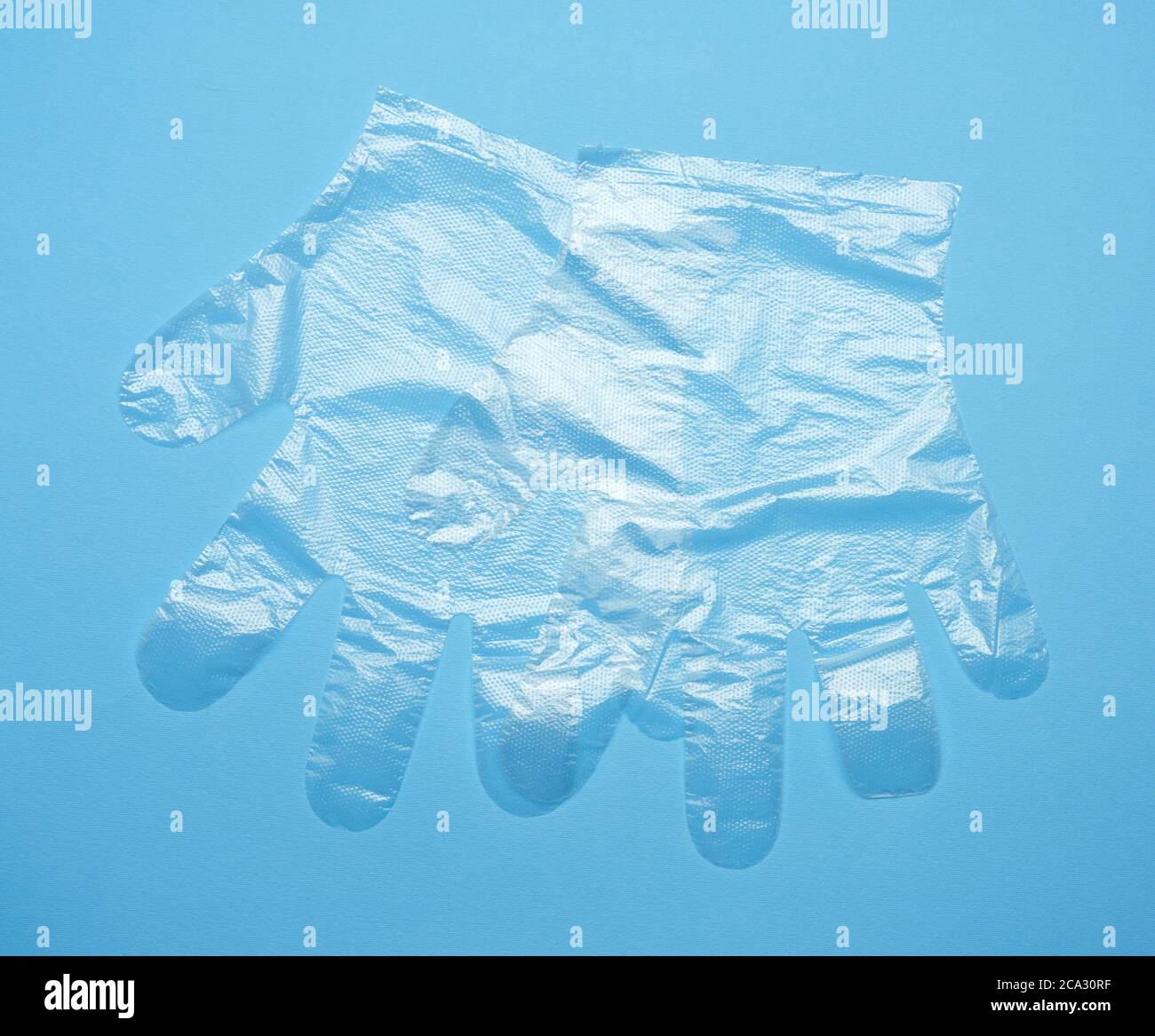 pair of disposable polyethylene gloves on a blue background, top view, flat lay. Stock Photo