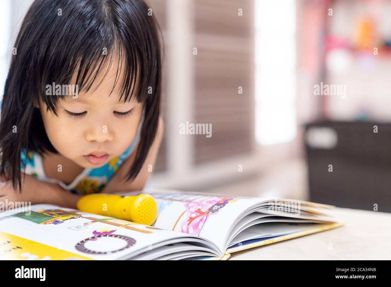 Asian girl child reading interactive book in living room at home as home schooling while city lockdown because of covid-19 pandemic across the world. Stock Photo