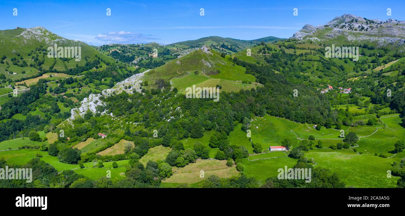 Spring landscape of mountains, meadows of mowing and cabins pasiegas in the Miera Valley, Cantabria, Spain, Europe. Stock Photo