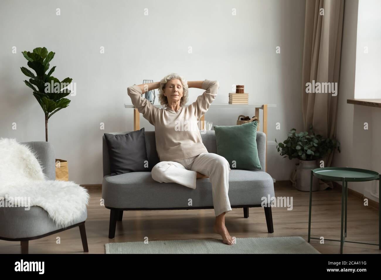 In living room on modern comfy couch relaxing mature woman Stock Photo
