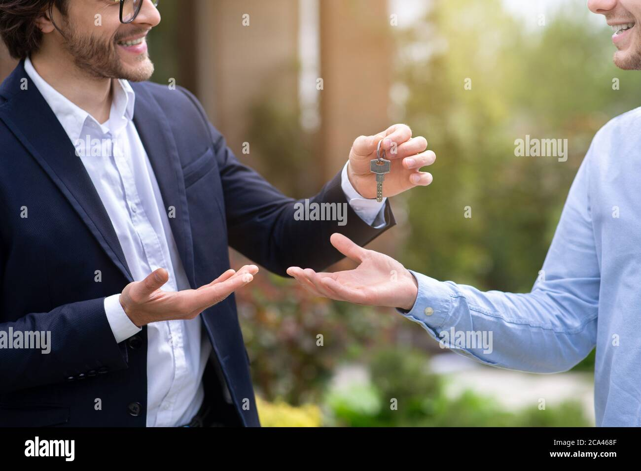 Cropped view of real estate agent giving house key to new home owner near his property, close up Stock Photo