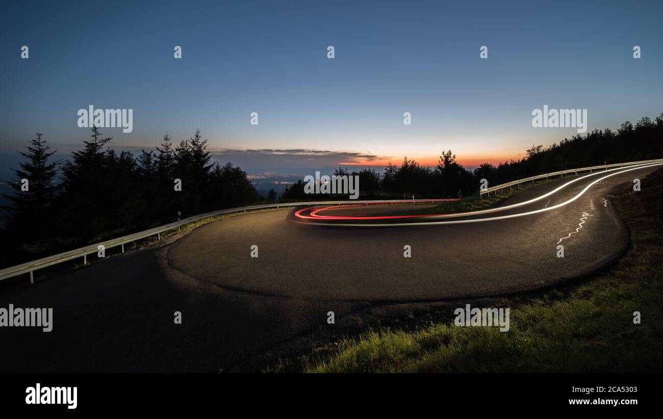 light trails at evening from cars in a curve in germany. Stock Photo