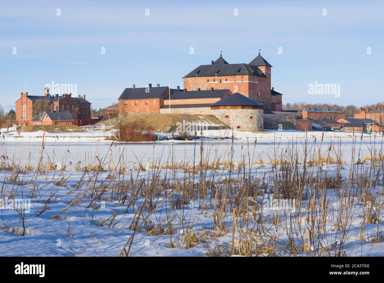 View of the ancient fortress of the city of Hameenlinna from the shore of Vanajavesi lake on a sunny March day. Finland Stock Photo