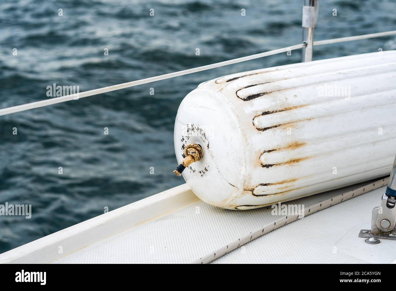 A detailed image of a boat fender on a sailboat with blue water in the Great Lakes. Stock Photo