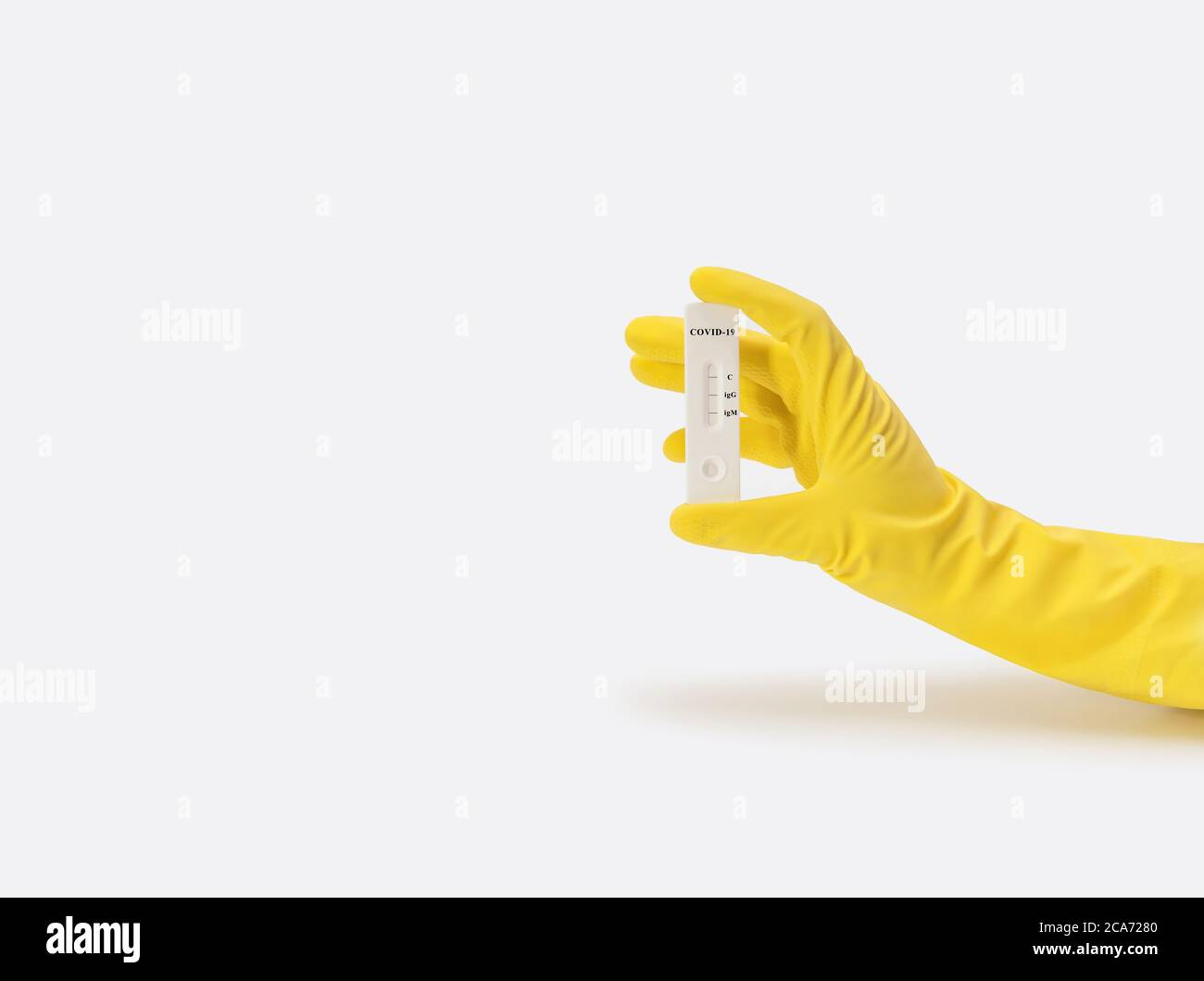 Coronavirus test in hand on a white background. Unused covid-19 test cassette. A hand in a yellow medical glove holds an express test. Copy space. Stock Photo