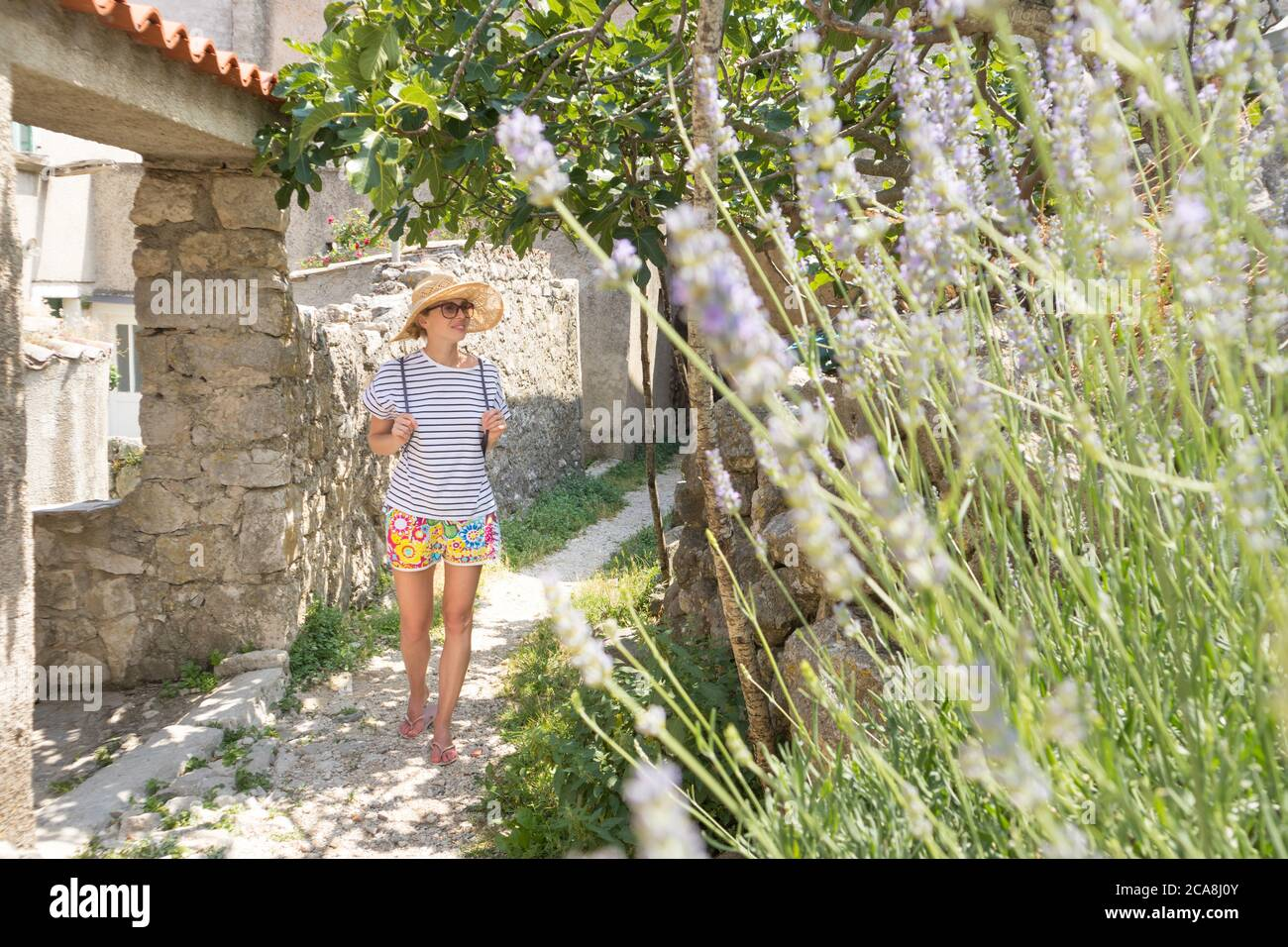 Rear view of beautiful blonde young female traveler wearing straw sun hat sightseeing and enjoying summer vacation in an old traditional costal town Stock Photo