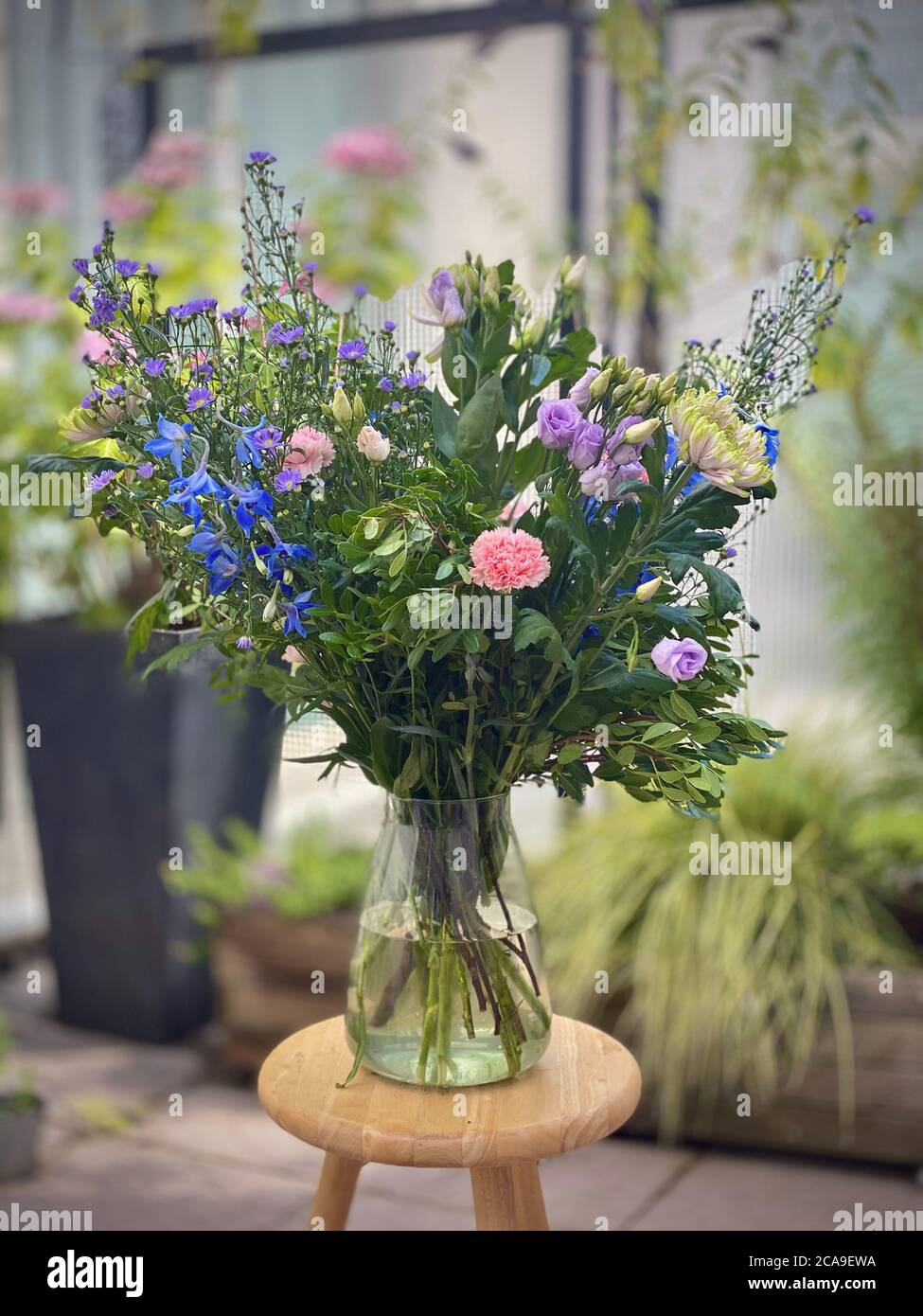 Beautiful Big Bouquet Of Flowers In A Vase Outside Displayed On A Small Wooden Table Plantlife Flowering Standing In Water Blurred Background Blue Purple And White Carnations Green Leafed Leaves Stock Photo Alamy