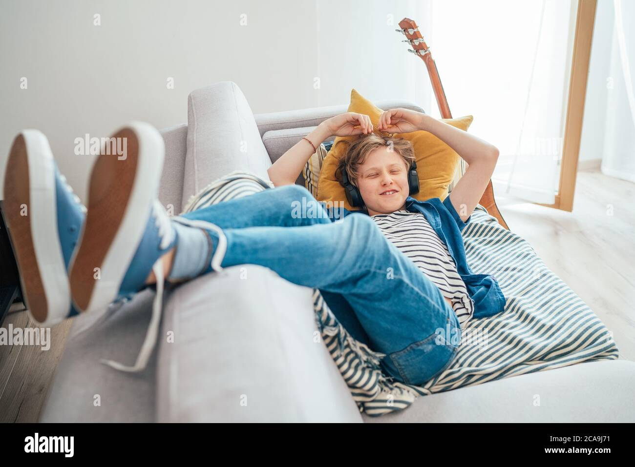Smiling Preteen boy lying at home living room filled with sunlight on cozy sofa dressed casual jeans and sneakers listening to music using wireless he Stock Photo