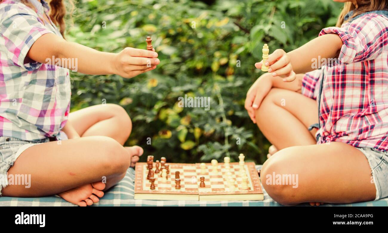 Play chess. Sisters playing chess. Children play chess outdoors nature background. Sport and hobby concept. Strategy concept. Cognitive development. Intellectual game. Make decision. Smart children. Stock Photo
