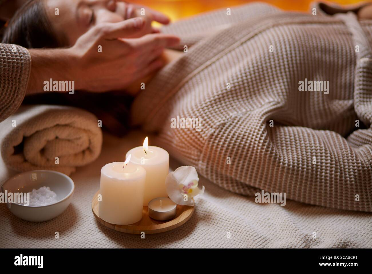 Young girl having massage on her face in spa salon. Wearing bathrobe, candles near her. Beauty treatment Stock Photo