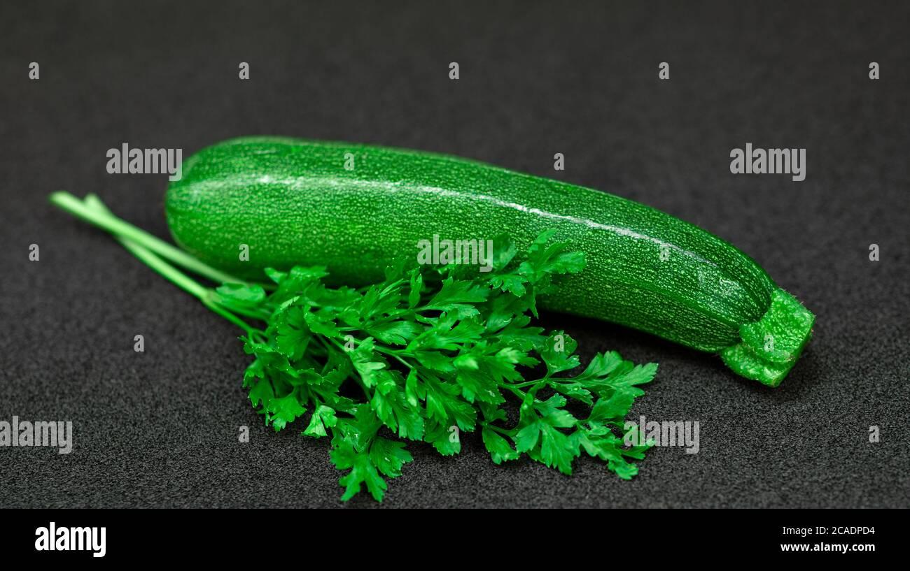 Fresh green zucchini and parsley on a dark background Stock Photo