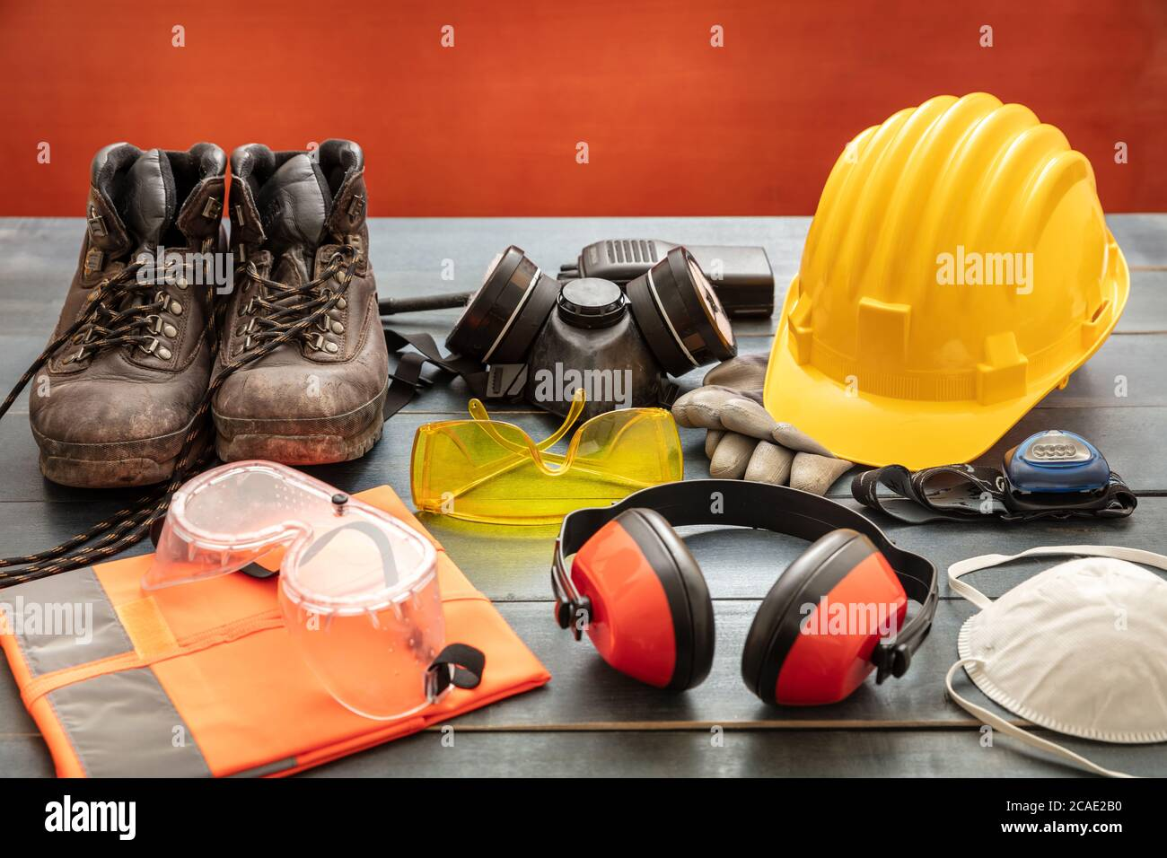 Work safety protection equipment. Industrial protective gear on wooden table, red color background. Construction site health and safety concept Stock Photo
