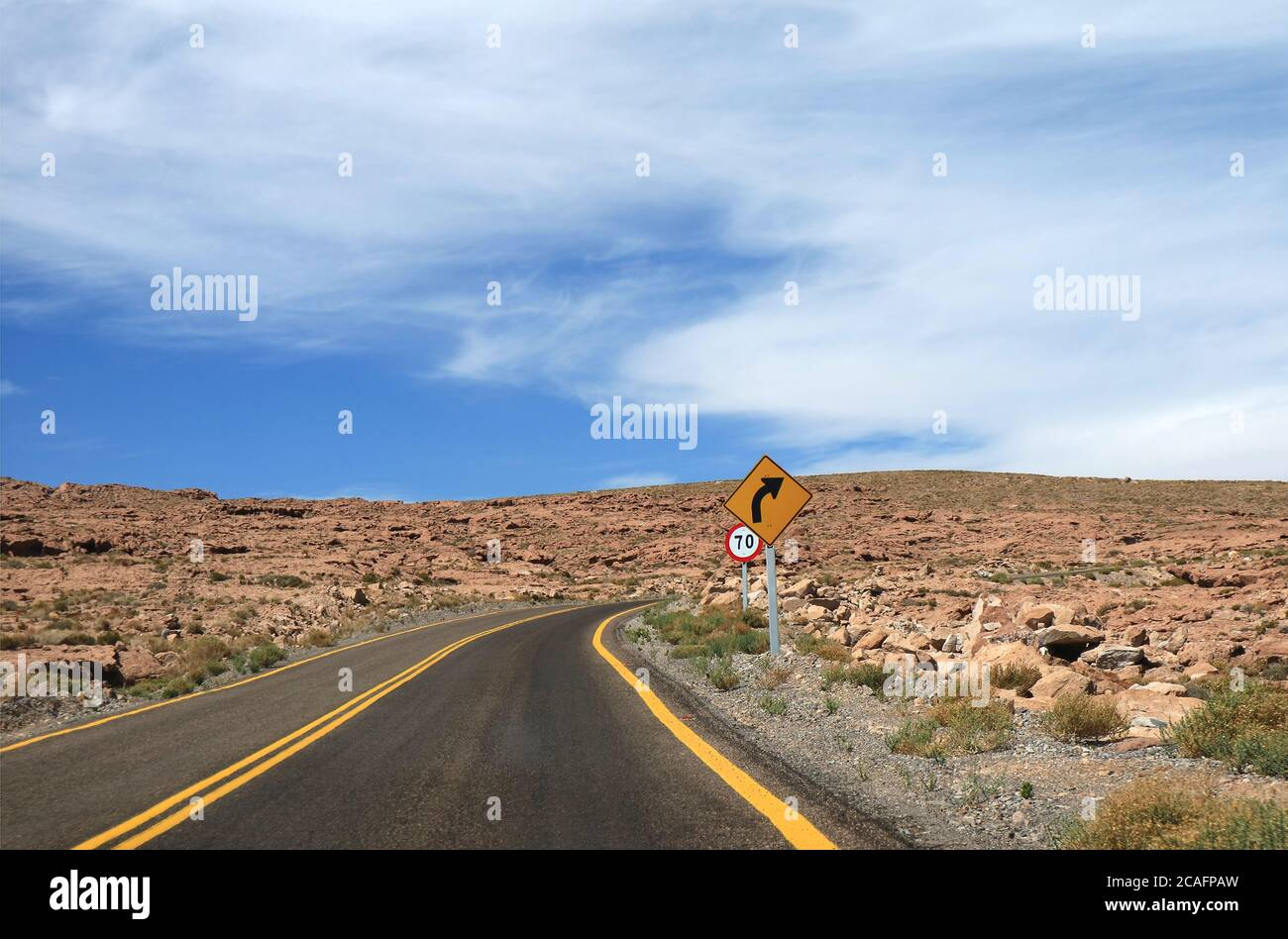 Right Curve and Speed Limit Traffic Signpost on the Empty Road in Atacama Desert, Los Flamencos National Reserve, Northern Chile, South America Stock Photo