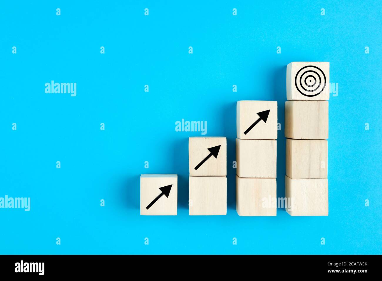 Business or economic growth concept with arrow icons on wooden cubes on blue background Stock Photo