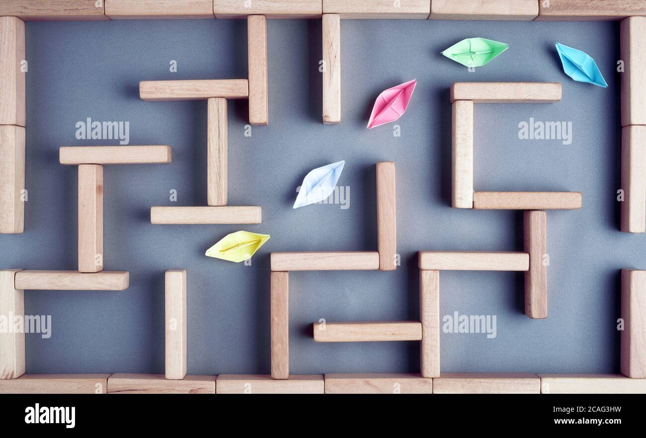Leadership, guidance or teamwork, concept. Colorful paper boats in line are moving towards the exit in a maze or labyrinth made with wooden blocks. Stock Photo