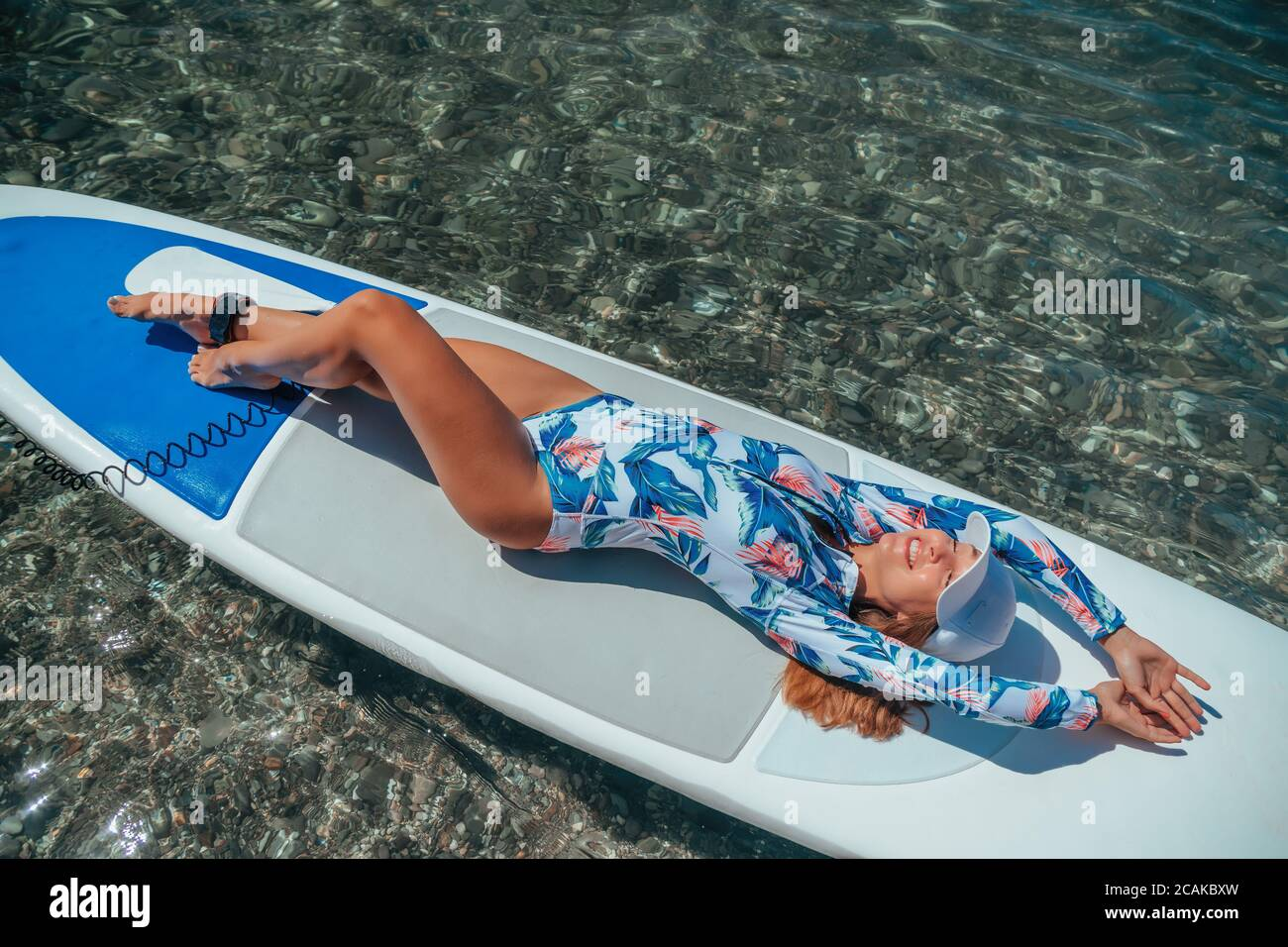 SUP Stand up paddle board. Young woman sailing on beautiful calm sea with crystal clear water. The concept of an summer holidays vacation travel Stock Photo