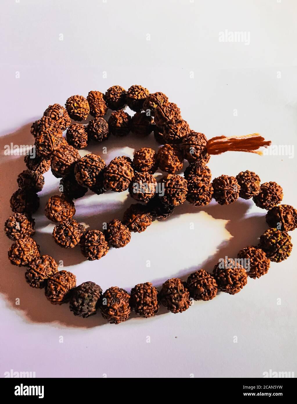 Rudraksha japa Mala or Prayer beads made from the seeds of the rudraksha tree on white background ,108 beads . Stock Photo