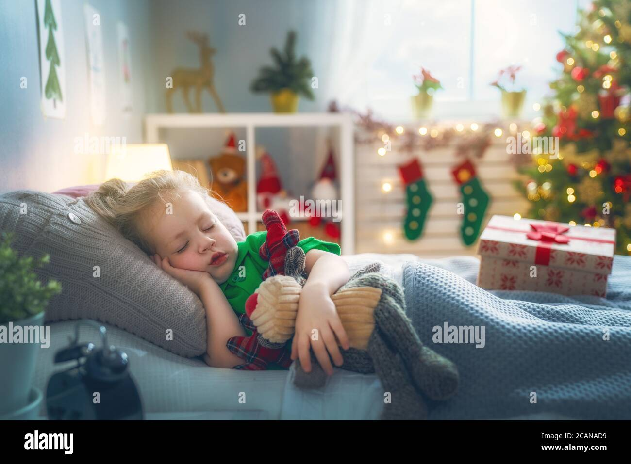 Merry Christmas and Happy Holiday! Cute little child girl sleeping in the bed near tree at home. Stock Photo