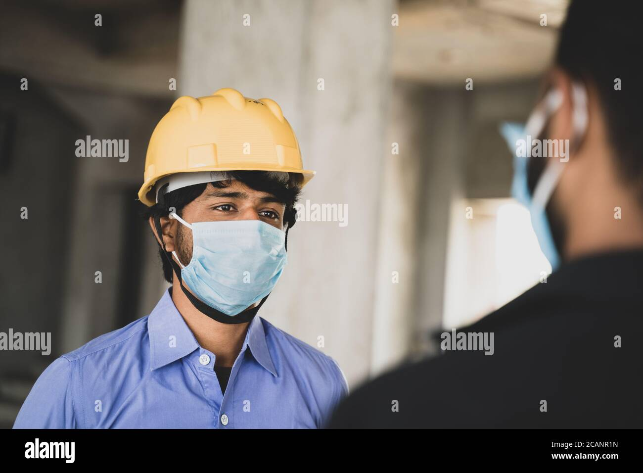 Two Construction workers or engineers at site talking by wearing medical face mask while maintaining social distance - concept of business, industry Stock Photo