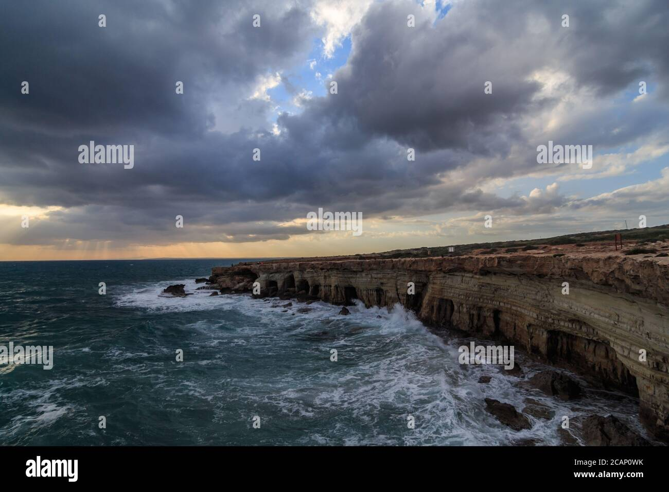 Sea Caves - Mediterranean Sea landscape near Ayia Napa, Cyprus during a stormy cloudy sunset Stock Photo