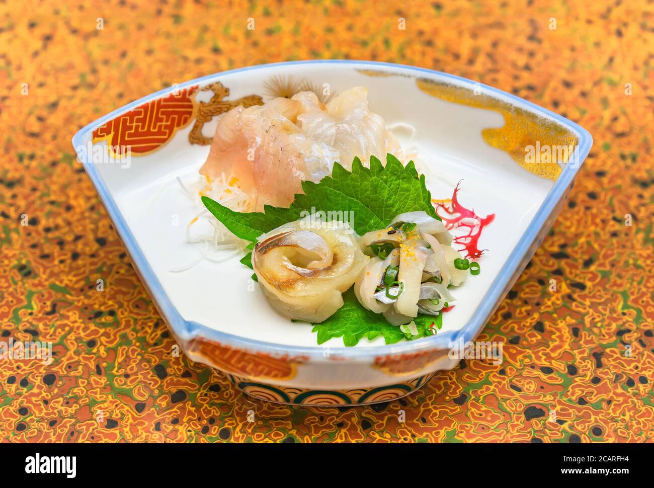 Raw sashimi high-class japanese cuisine of fresh Sayori needlefish, Madai seabream and Hirame halibut in a dish plate with Gracilaria red algae Stock Photo