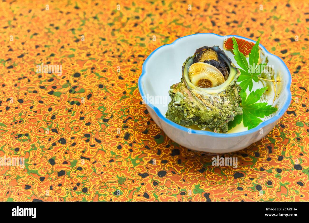 High-class japanese cuisine of traditional Tsubo-yaki steamed Sazae horned turban sea snail in a dish plate decorated with maple momiji leaves. Stock Photo